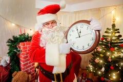 圣诞老人在他的手上的拿着一块手表,指向时钟a 免版税库存照片