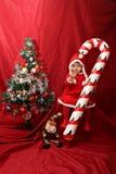 圣诞老人女孩、过大的棒棒糖和圣诞树 免版税库存照片