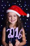 圣诞老人女孩拿着2016个纸图,圣诞节 免版税库存照片
