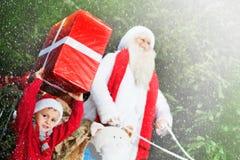 圣诞老人小的帮手在一雪天带来礼物 免版税库存照片