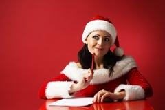 圣诞老人帮手帽子和圣诞老人的微笑的妇女穿衣与铅笔和纸在红色背景 库存照片