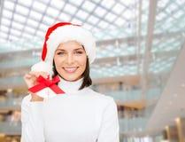 圣诞老人帮手帽子和门铃的微笑的妇女 库存图片