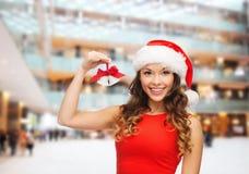 圣诞老人帮手帽子和门铃的微笑的妇女 免版税库存照片