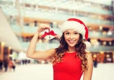 圣诞老人帮手帽子和门铃的微笑的妇女 图库摄影