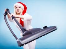 圣诞老人帮手帽子的女孩有吸尘器的 免版税库存图片