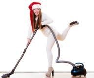 圣诞老人帮手帽子的女孩有吸尘器的 免版税库存照片
