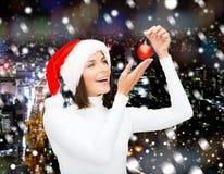 圣诞老人帮手帽子的妇女有圣诞节球的 图库摄影