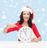 圣诞老人帮手帽子的妇女有显示12的时钟的 库存图片