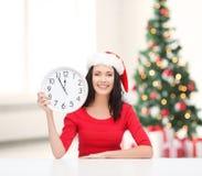 圣诞老人帮手帽子的妇女有显示12的时钟的 免版税库存图片