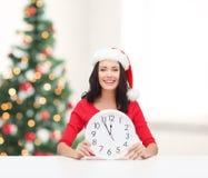 圣诞老人帮手帽子的妇女有显示12的时钟的 图库摄影