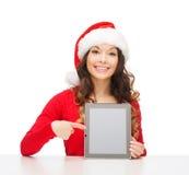 圣诞老人帮手帽子的妇女有片剂个人计算机的 图库摄影