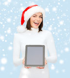 圣诞老人帮手帽子的妇女有片剂个人计算机的 免版税库存照片