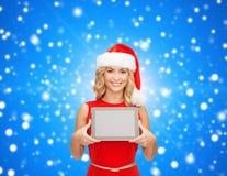 圣诞老人帮手帽子的妇女有片剂个人计算机的 库存图片