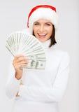 圣诞老人帮手帽子的妇女有的美元金钱 库存图片