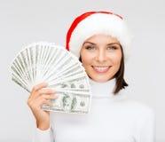 圣诞老人帮手帽子的妇女有的美元金钱 图库摄影