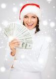 圣诞老人帮手帽子的妇女有的美元金钱 免版税库存图片