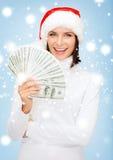 圣诞老人帮手帽子的妇女有的美元金钱 免版税库存照片