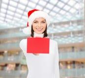 圣诞老人帮手帽子的妇女有空白的红牌的 库存照片