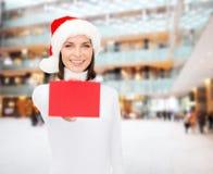 圣诞老人帮手帽子的妇女有空白的红牌的 免版税库存照片