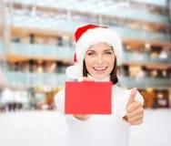 圣诞老人帮手帽子的妇女有空白的红牌的 免版税库存图片