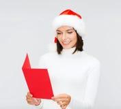 圣诞老人帮手帽子的妇女有空白的红色明信片的 免版税库存图片