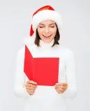 圣诞老人帮手帽子的妇女有空白的红色明信片的 库存照片