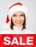 圣诞老人帮手帽子的妇女有红色销售标志的 库存图片