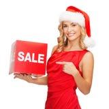 圣诞老人帮手帽子的妇女有红色销售标志的 免版税库存照片