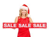 圣诞老人帮手帽子的妇女有红色销售标志的 免版税库存图片