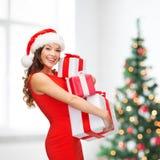 圣诞老人帮手帽子的妇女有许多礼物盒的 库存照片