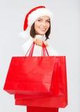 圣诞老人帮手帽子的妇女有购物袋的 图库摄影