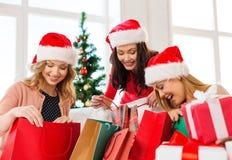 圣诞老人帮手帽子的妇女有购物袋的 库存照片