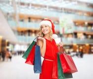 圣诞老人帮手帽子的妇女有购物袋的 免版税库存图片