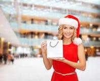 圣诞老人帮手帽子的妇女有购物袋的 免版税库存照片