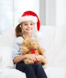 圣诞老人帮手帽子的微笑的女孩有玩具熊的 库存照片