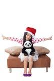 圣诞老人帮手帽子的微笑的女孩有玩具熊的 免版税库存照片