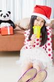 圣诞老人帮手帽子的微笑的女孩有玩具熊的 图库摄影