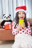 圣诞老人帮手帽子的微笑的女孩有玩具熊的 库存图片