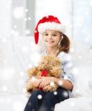 圣诞老人帮手帽子的微笑的女孩有玩具熊的 免版税库存图片
