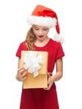 圣诞老人帮手帽子的微笑的女孩有礼物盒的 免版税库存照片