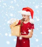 圣诞老人帮手帽子的微笑的女孩有礼物盒的 库存图片