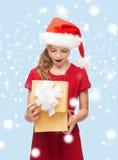 圣诞老人帮手帽子的微笑的女孩有礼物盒的 库存照片
