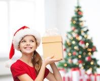 圣诞老人帮手帽子的微笑的女孩有礼物盒的 免版税库存图片