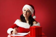 圣诞老人帮手帽子的微笑的妇女和有铅笔和纸和礼物盒的圣诞老人衣裳-加速圣诞节礼物 库存照片
