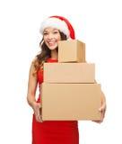 圣诞老人帮手帽子的微笑的妇女有小包的 免版税库存照片