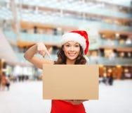 圣诞老人帮手帽子的微笑的妇女有小包箱子的 图库摄影