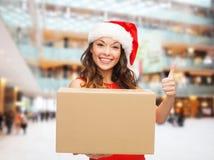 圣诞老人帮手帽子的微笑的妇女有小包箱子的 库存图片