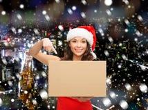 圣诞老人帮手帽子的微笑的妇女有小包箱子的 库存照片