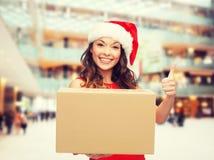 圣诞老人帮手帽子的微笑的妇女有小包箱子的 免版税图库摄影