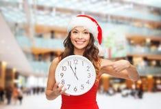 圣诞老人帮手帽子的微笑的妇女有时钟的 图库摄影